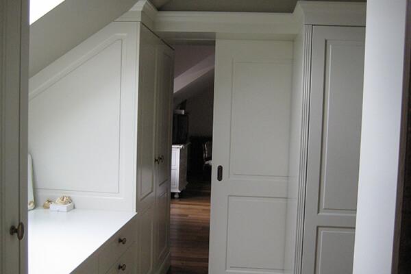 Toegang via een schuifdeur naar een dressing op een zolderruimte