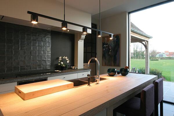 een houten werkblad en zwarte wand in een prachtige tijdloze keuken