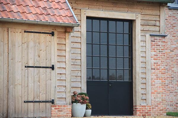 Zwart aluminium voordeur in contrast met houten gevelbekleding
