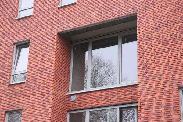 Grijs aluminium schrijnwerk contrastreert met hedendaagse appartementsbouw
