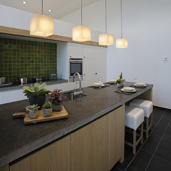 Een langwerpig kookeiland biedt werkruimte in een tijdloze keuken