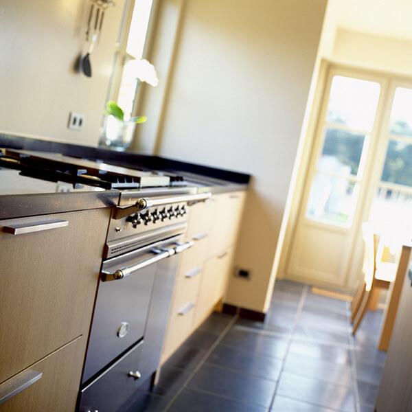 Een langwerpig keukeneiland in hout met witte kastdeuren